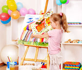 Child painting at easel in school — Stock Photo