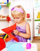 Child cutting out scissors paper in kindergarten — Stock Photo