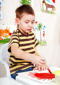 Child with picture and brush in play room. — Stock Photo
