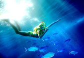 Child scuba diver with group coral fish. — Stock Photo