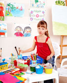 Little girl with picture and brush in playroom — Stock Photo