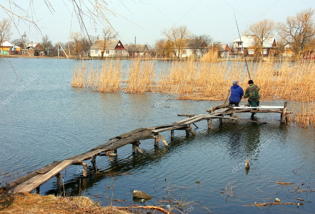 Two men on the bridge fish in farm pond  Stock Photo #11867460