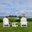 Single senior man in white chairs overlooking bay — Stock Photo #10810122