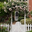 Foto Stock: Wild flowers growing over white picket fence