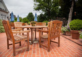 Teak patio tables and chairs on brick deck — Stock Photo