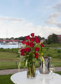 Bunch of roses with white wine and harbor — Stock Photo