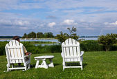 Single senior man in white chairs overlooking bay — Stock Photo