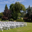 Rows of wooden chairs set up for wedding — Stock Photo