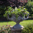 Large stone urn with plants in english garden — Stock Photo