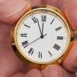 Brass small watch or clock in fingers — Stock Photo