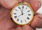 Petite montre de laiton ou d'horloge dans les doigts — Photo