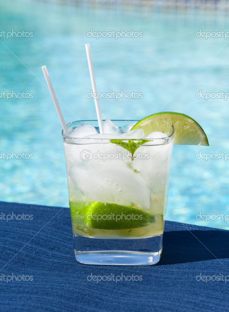 Glass of ice cold majito in glass by side of swimming pool — Stock Photo #11369003
