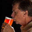Senior man sipping from pint glass beer — Stock Photo #11460409