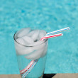 Glass of water with ice cubes on side of pool — Stock fotografie