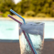 Glass of water with ice cubes on side of pool — Stok fotoğraf