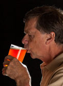 Senior man sipping from pint glass beer — Stock Photo