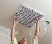 Homem sênior, abrindo o filtro de ar condicionado no teto — Foto Stock