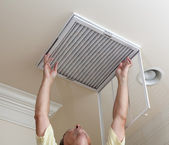 Senior man opening air conditioning filter in ceiling — Стоковое фото