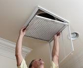 Senior homme climatisation filtre d'ouverture dans le plafond — Photo