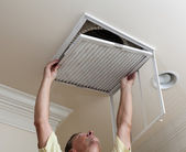 Uomo anziano filtro aria condizionata di apertura nel soffitto — Foto Stock