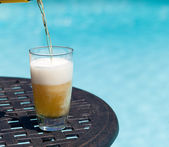 Glass of beer on table by poolside — Stock Photo