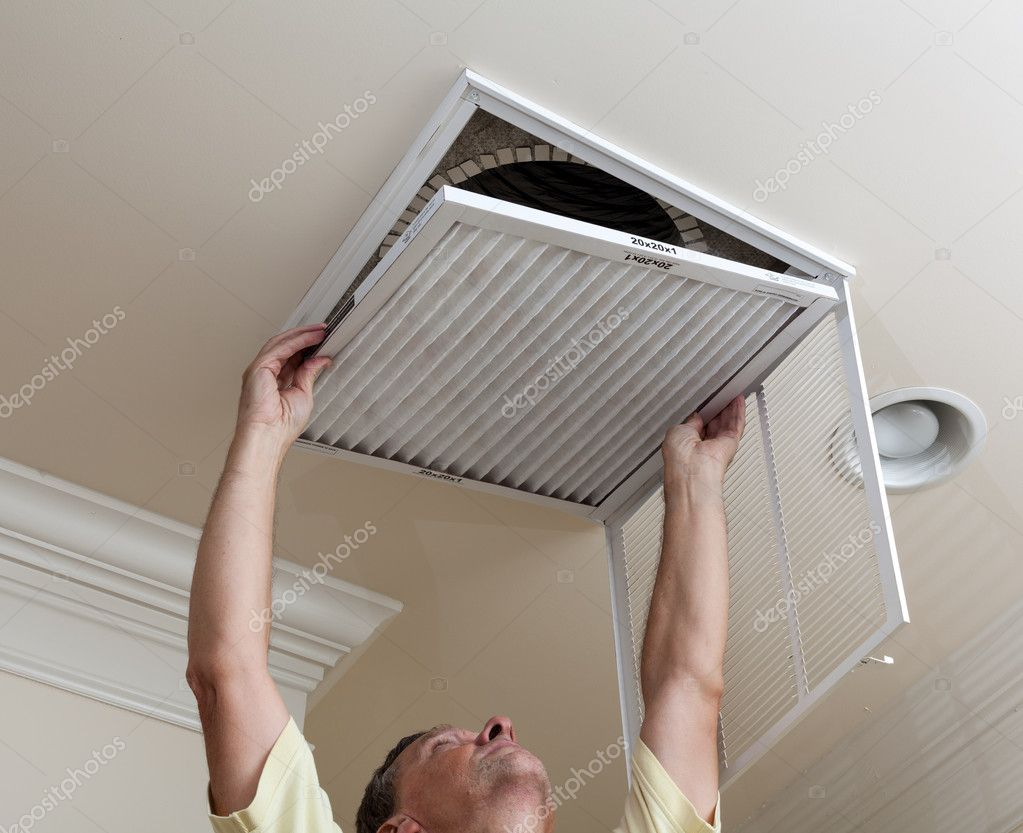 Senior male reaching up to open filter holder for air conditioning filter in ceiling — Stock Photo #11461285