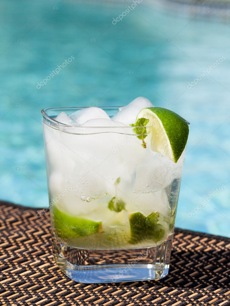 Glass of ice cold majito in glass by side of swimming pool — Stock Photo #11461322