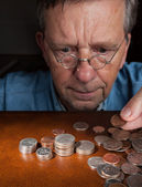Senior man counting cash into piles — Stock Photo