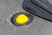 Egg on hot road surface beginning to fry — Stock Photo