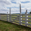 White picket fence in garden to rural meadow — Stockfoto