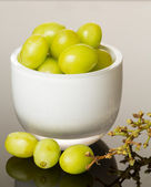 White glass bowl full of green grapes — Stock Photo