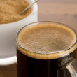 Black coffee and froth in glass mug with sugar — Stock Photo