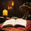 Paperback book open on chair by fire and candle — Stock Photo