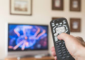 Close up of TV remote control with television — Stock Photo