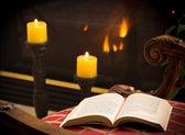 Karton kapaklı kitap açık ateş ve mum sandalyenin üzerinde — Stok fotoğraf