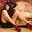 Beautiful woman sitting on the floor near vintage couch. — Stock Photo