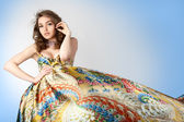 Portrait of the young beautiful girl in colorful dress. — Stock Photo