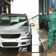 Stock Photo: Worker cleaning car with pressured water