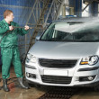Worker cleaning car with pressured water — Stock Photo