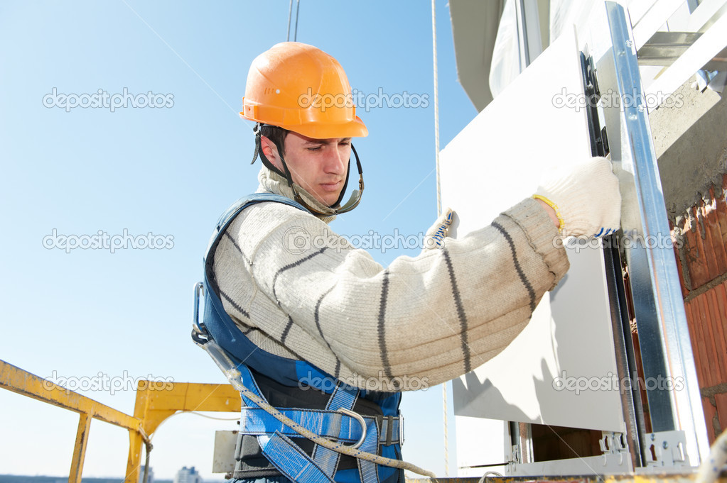 Worker builderinstalling big tile on aerated facade constructiona of building — Stock Photo #11135535