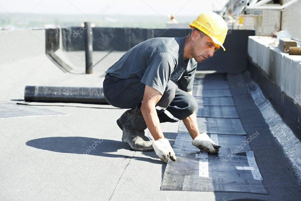 Roofer preparing part of bitumen roofing felt roll for melting by gas heater torch flame  Zdjcie stockowe #11135600