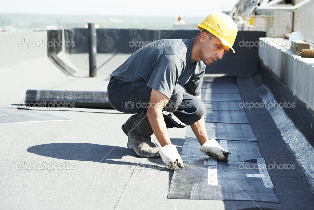 Roofer preparing part of bitumen roofing felt roll for melting by gas heater torch flame    #11135600