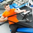 Bodybuilder man doing exercises in fitness club - Stock Photo