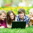 Young students group with computer outdoors — Stock Photo