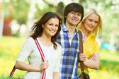 Three young students group outdoors — Stock Photo