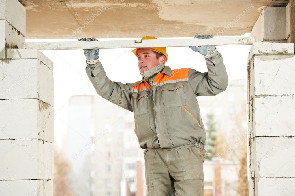 Mason worker bricklayer builder examinng bricklaying with construction equipment level — Stock Photo #11181360