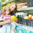 Stock Photo: Woman and little girl shopping fruits