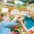 Woman and little girl shopping fruits — Stock Photo #11237867