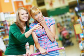 Two shopping woman with cart at supermarket — Stock Photo