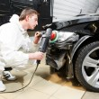 Mechanic repairing and polishing car headlight - Stock Photo